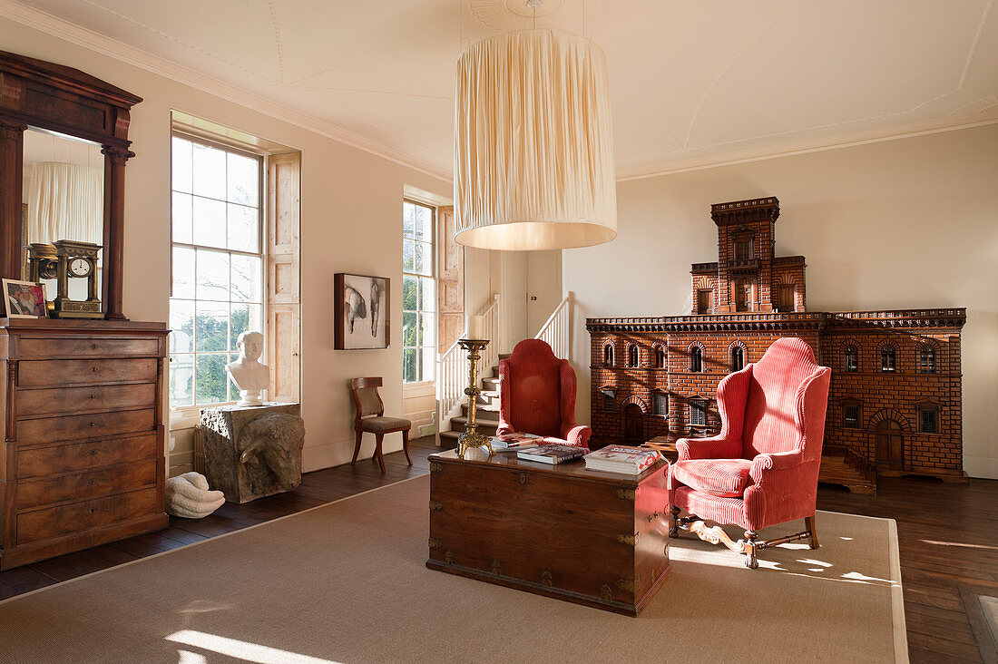 A pair of antique red corduroy wing chairs in sitting room with regency chest of drawers and a model Italian palazzo