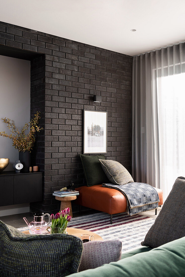 Leather stool in front of black brick wall in the living room