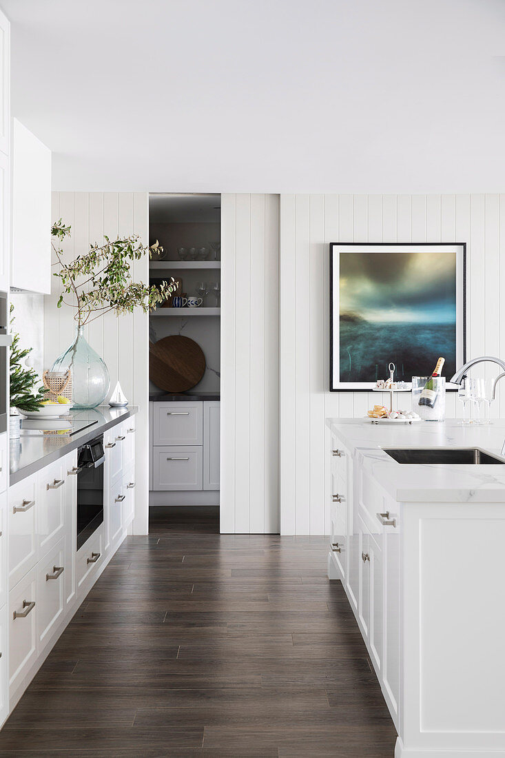 Glance into bright contemporary kitchen with white kitchen unit and kitchen island