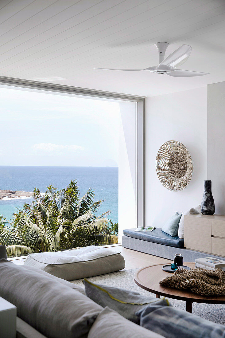 Living room in natural tones with panoramic windows to the sea