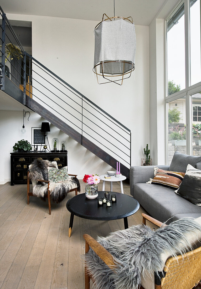 Grey couch in seating area and stairs leading to gallery in double-height interior