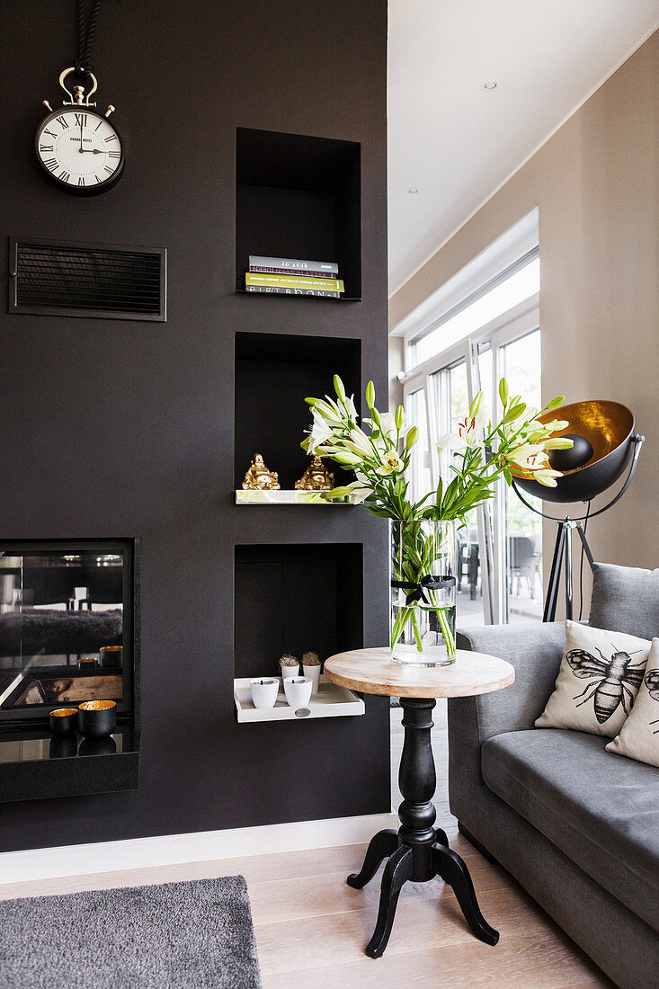 Vase of lilies on side table in front of partition wall in living room