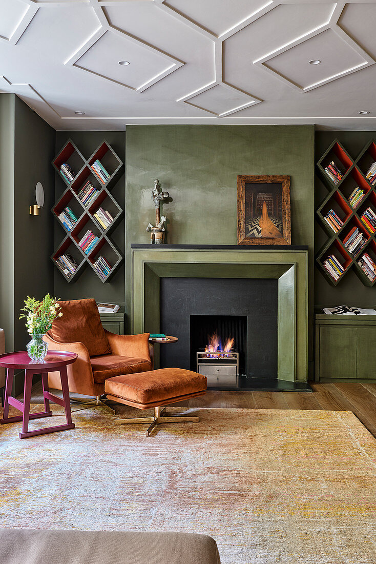 Armchair and footstool next to fireplace and diamond-shaped bookshelves