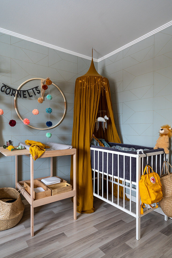 Changing table and cot in room with pale grey walls