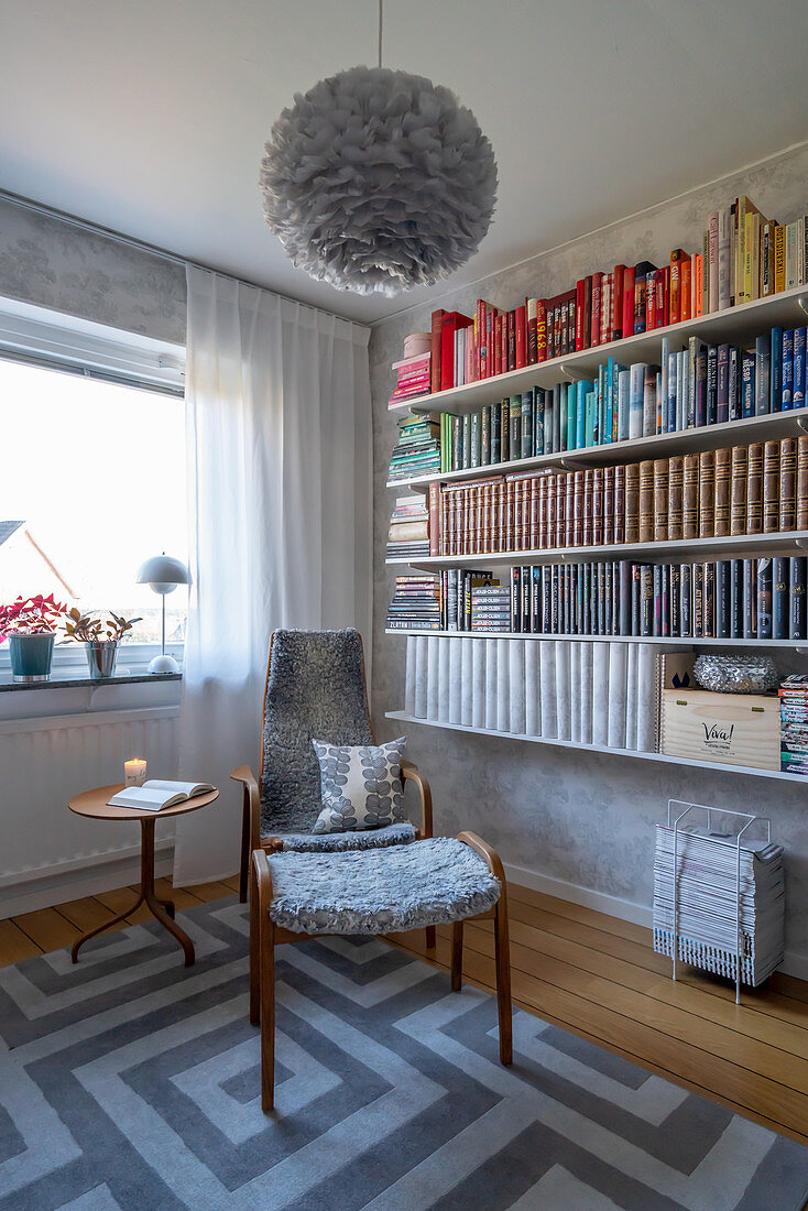 Books sorted by colour on shelves above retro armchair