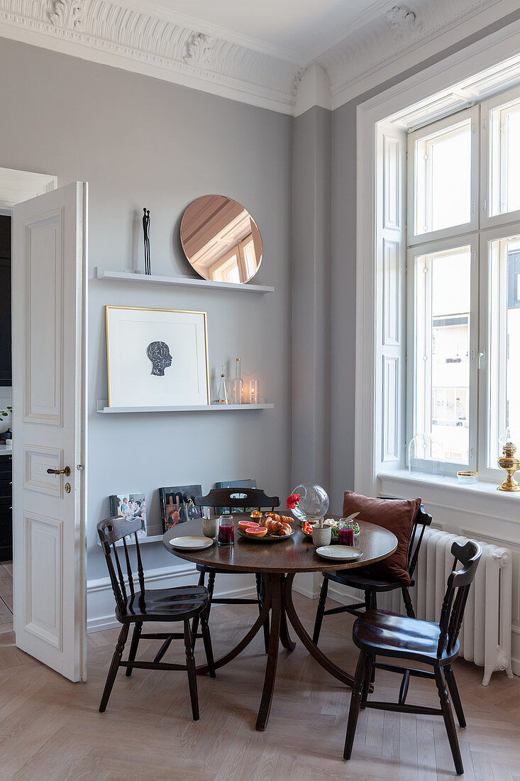 Round dining table with wooden chairs in corner of renovated period apartment