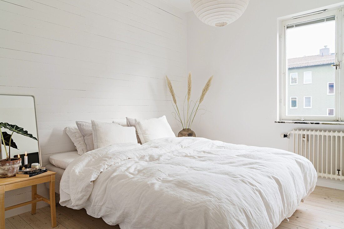 Double bed with white bed linen in white bedroom