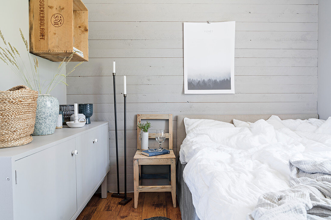 Grey board wall behind bed in rustic bedroom