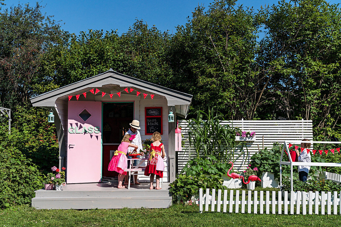 Play house in American fifties style and children playing in garden