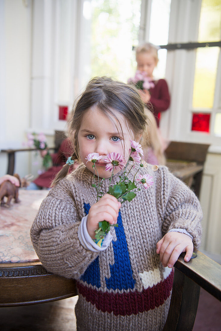 Girl wearing knitted sweater smelling posy