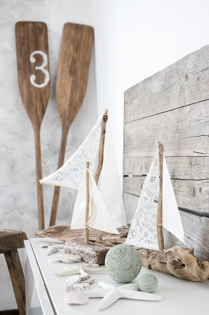 Sailing boat ornaments made from driftwood and fabric remnants next to paddles in corner