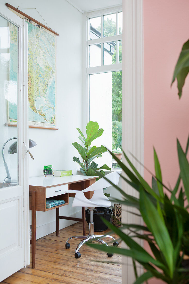 Desk below map on wall in conservatory