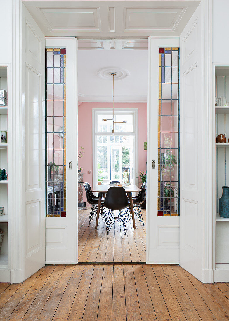 View through open, double, sliding doors with stained-glass inserts leading into dining room