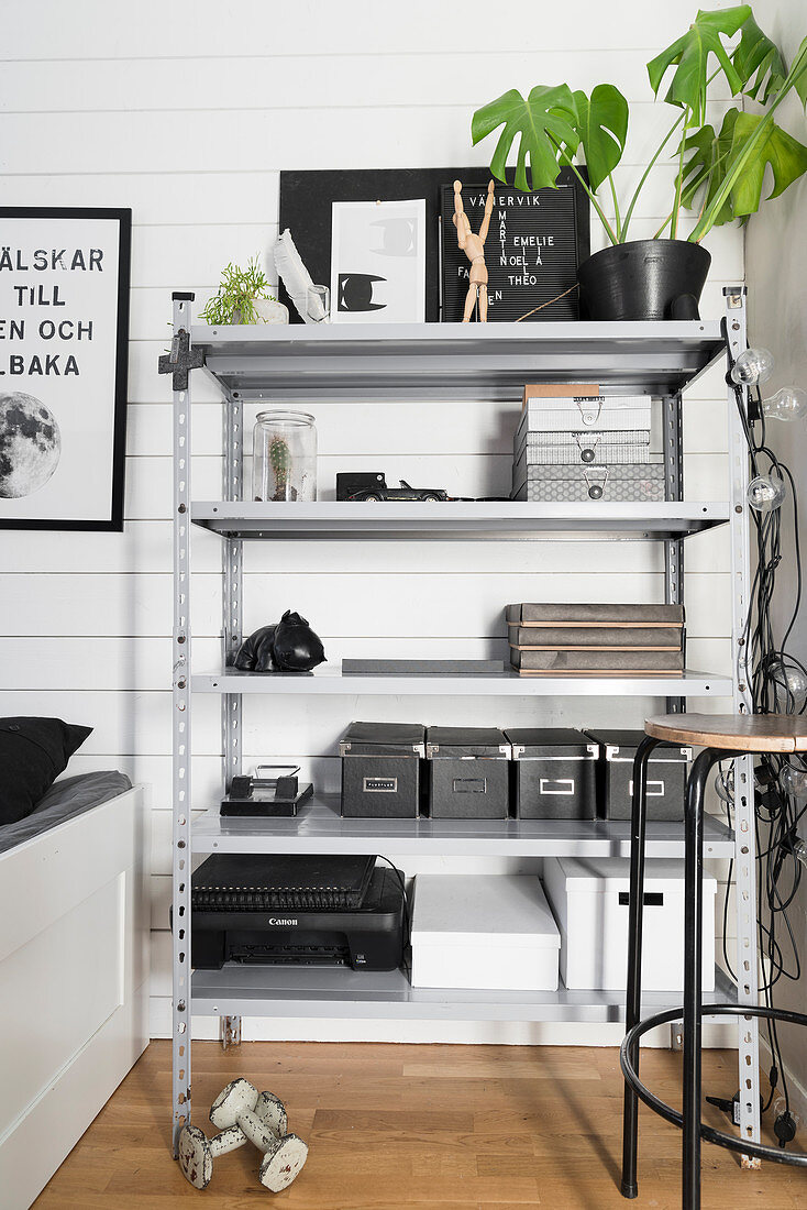Boxes and office utensils on grey metal shelves
