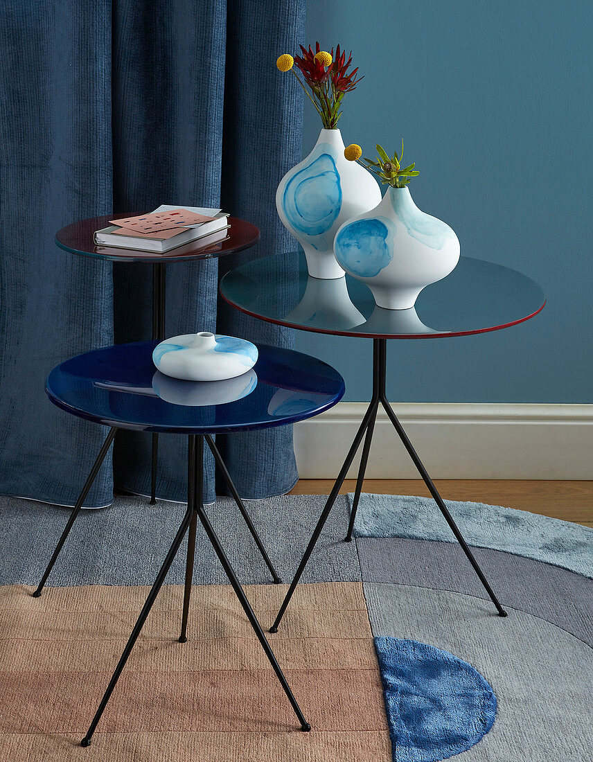 White vases with blue watercolour designs on round side tables
