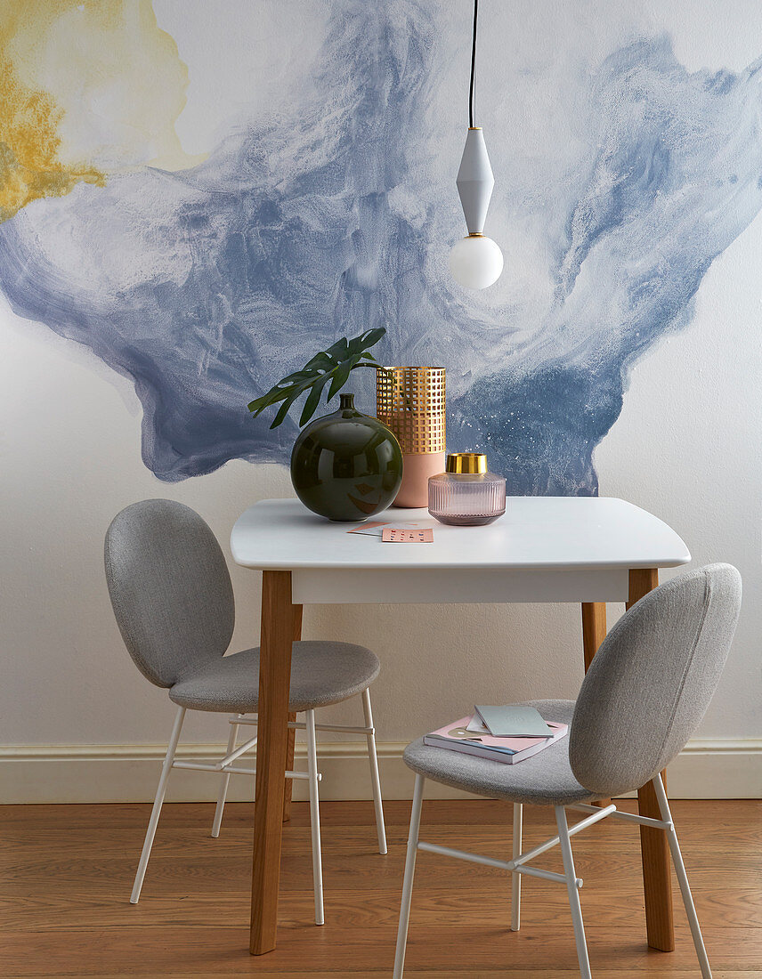 Upholstered chairs and table in front of watercolour-effect panel on wall