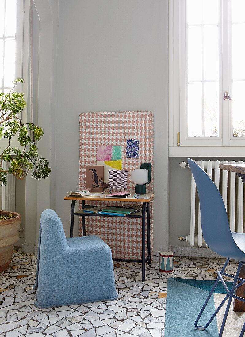 Blue felt chair at vintage school desk against patterned wall panel