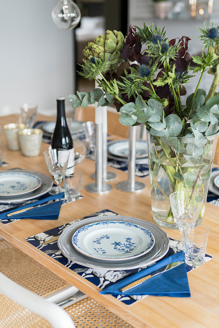 Vase of artichokes, thistles and eucalyptus on set dining table