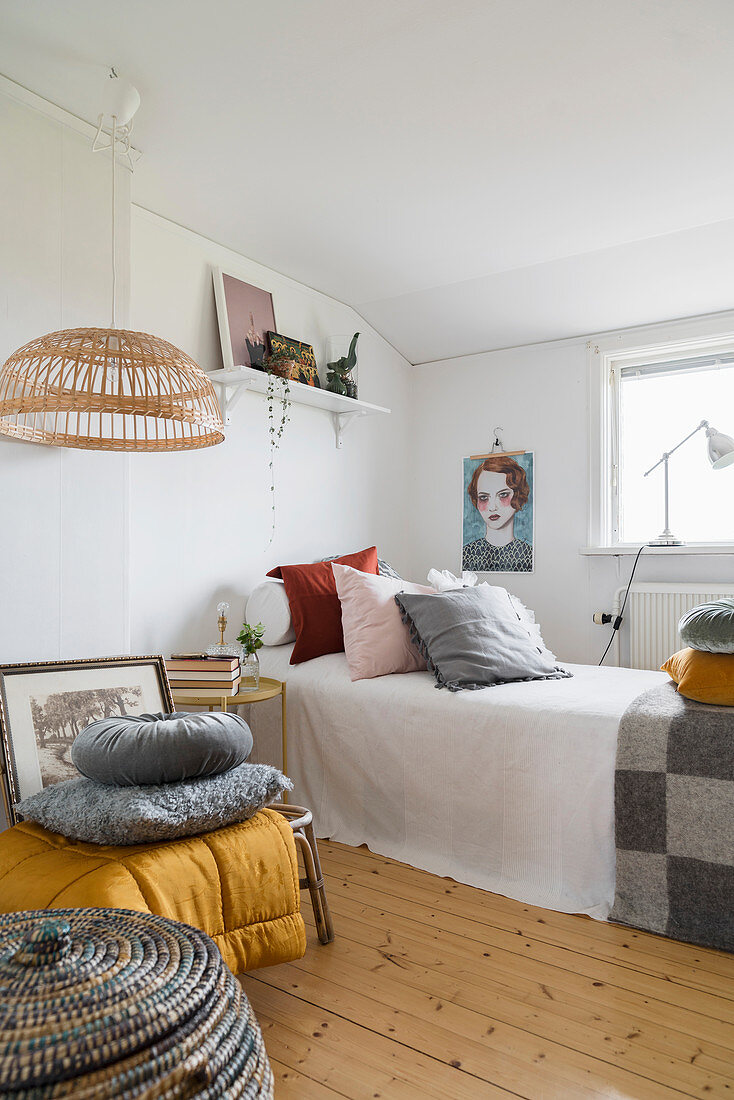 Scatter cushions on single bed in white guest room with wooden floor