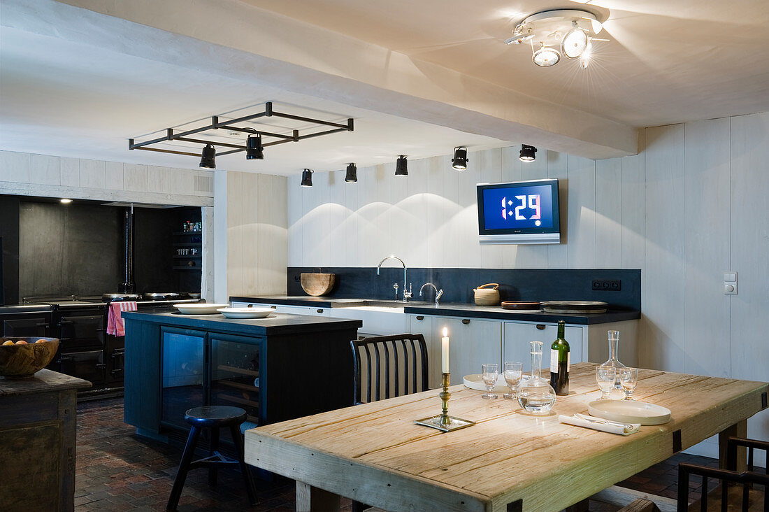 Island counter, rustic wooden table and various spotlights in black-and-white kitchen