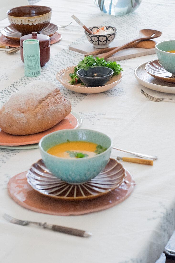 Möhrensuppe in türkisfarbenem Schälchen und Brot auf gedecktem Tisch