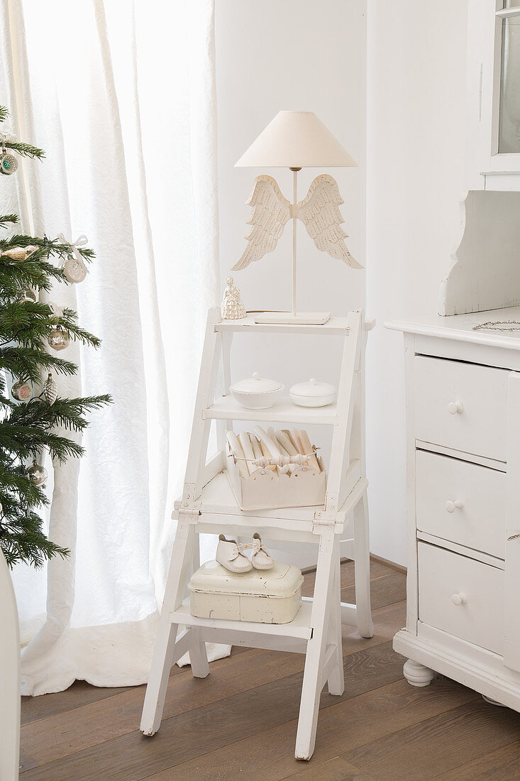White vintage-style ornaments on white-painted step ladders used as shelves