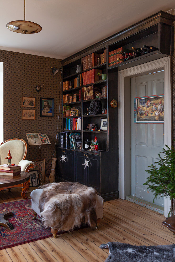 Floor-to-ceiling bookcase in dark wood, antique sofa and fur blanket on ottoman