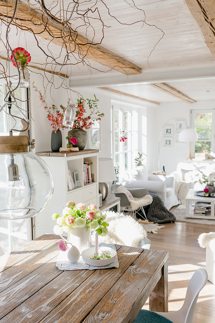 Vase of flowers on rustic dining table with lounge in background in open-plan interior