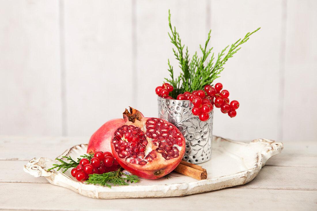 Stillleben mit Granatapfel und roten Johannisbeeren