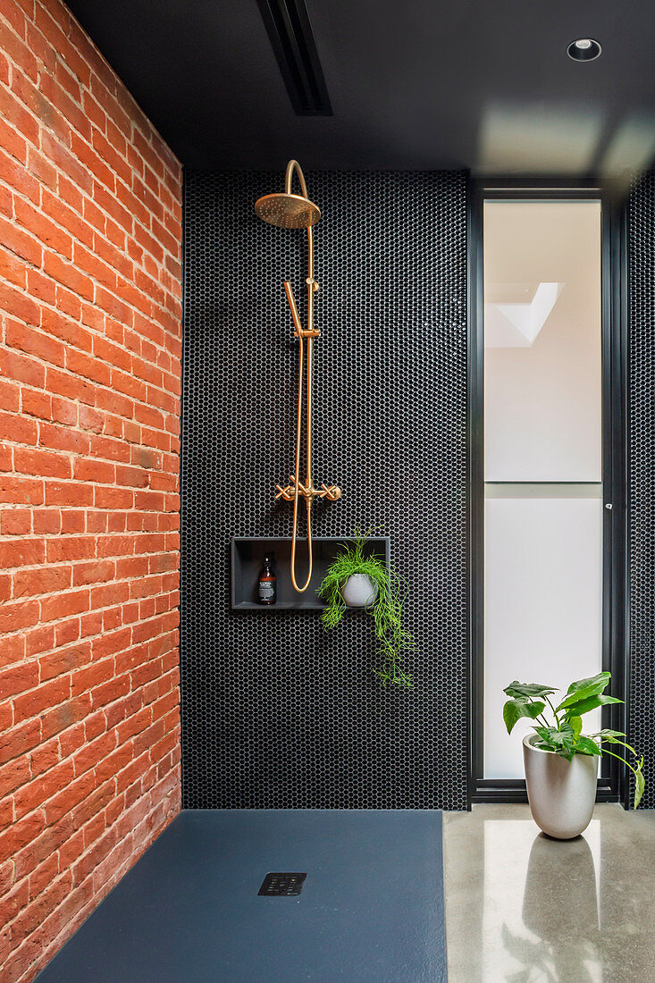 Black bathroom with red brick wall and walk-in shower area