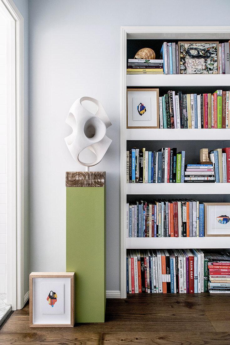 Abstract sculpture on green pillar next to bookshelf