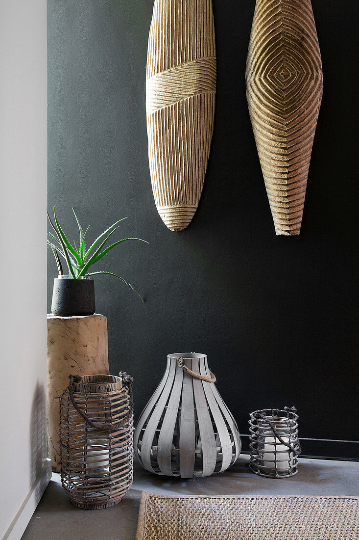 Exotic candle lanterns below ethnic decorations on black wall