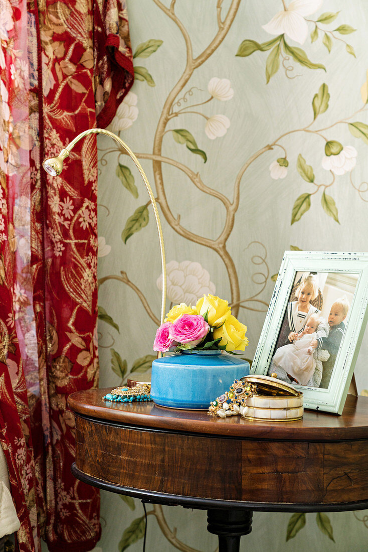 Posy of roses, jewellery box and family photo on antique side table