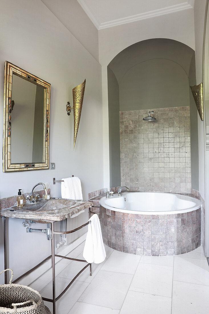 Round bathtub below archway in modern, Oriental bathroom