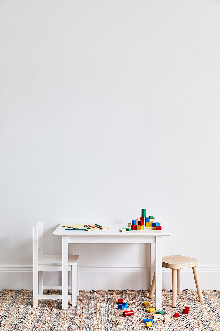 Colourful building blocks on and next to child's table with chair and stool
