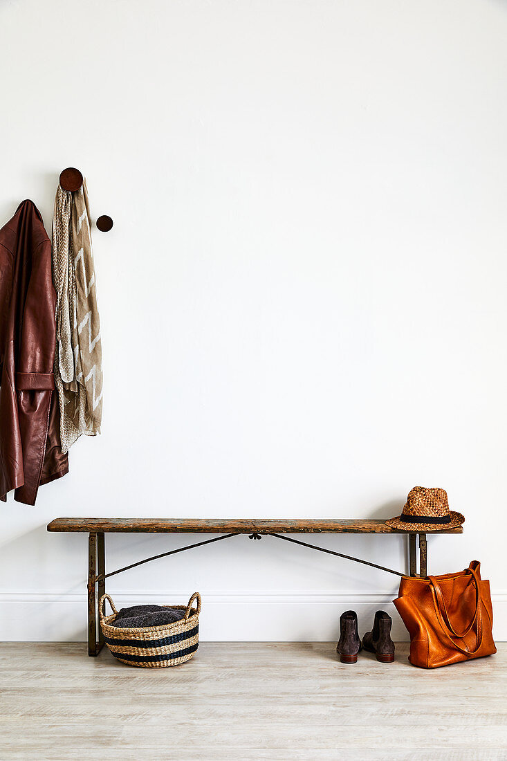 Old wooden bench in hall next to coat pegs
