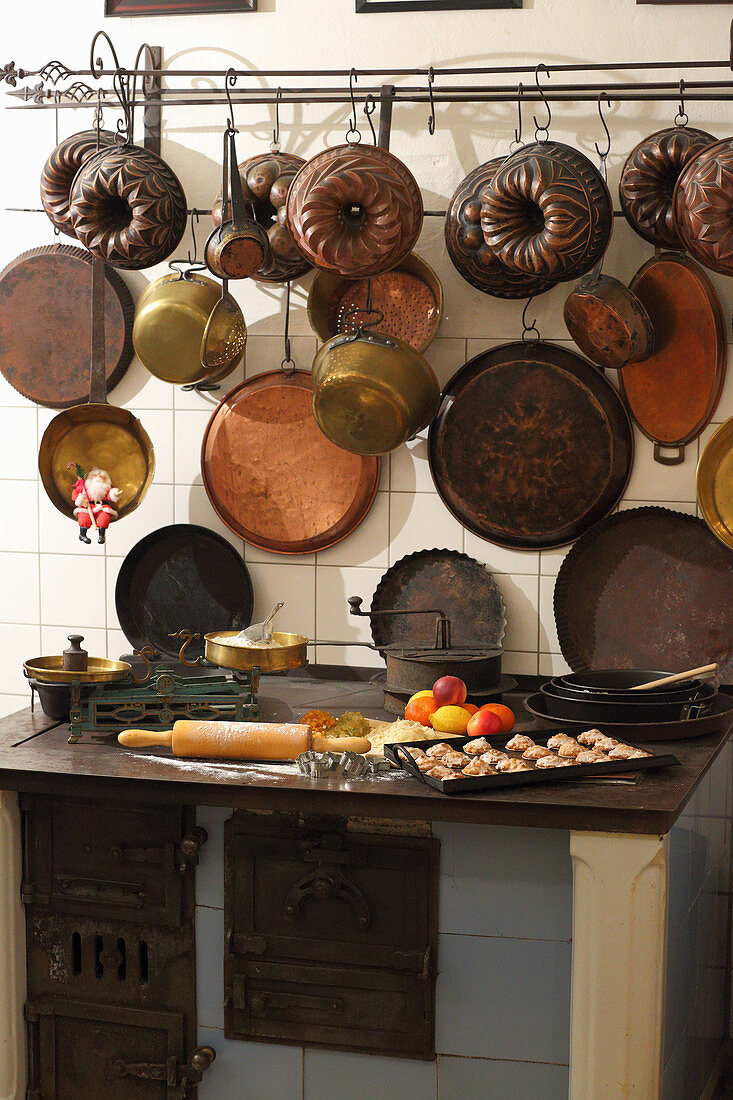 Biscuits and baking ingredients on old wood-fired stove below vintage pans and cake tins on wall in kitchen