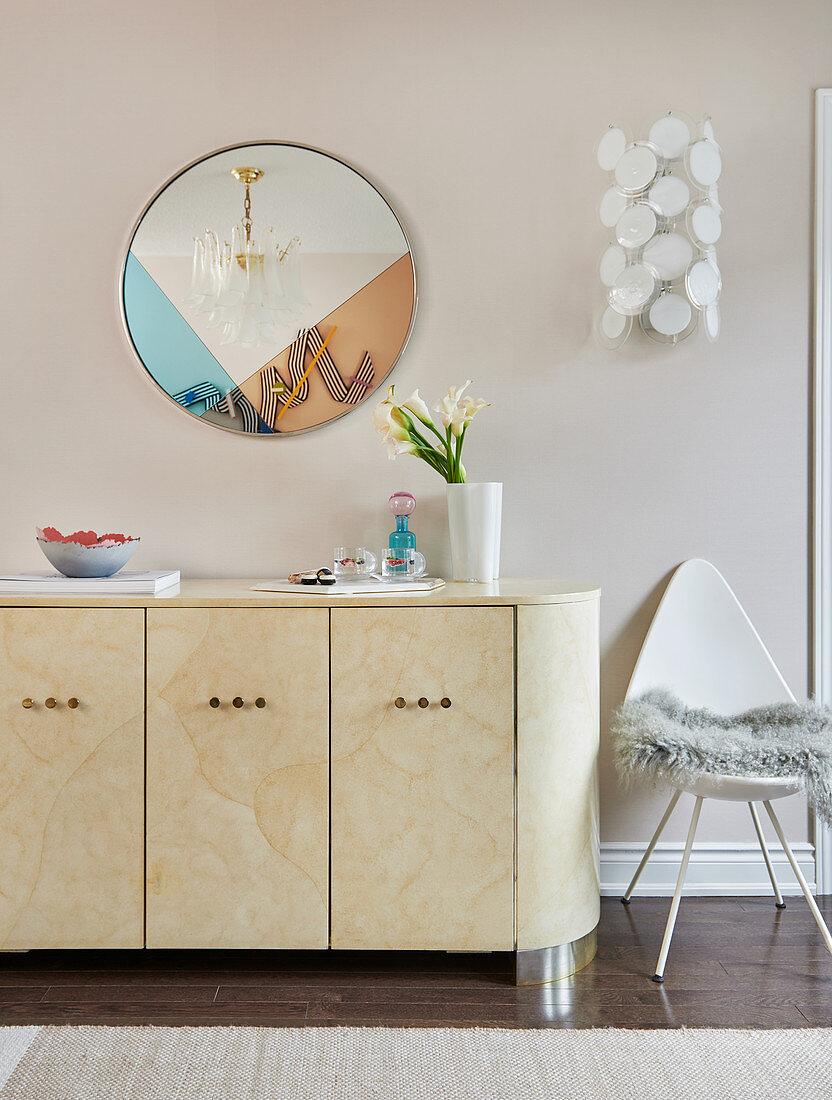 Round mirror above sideboard