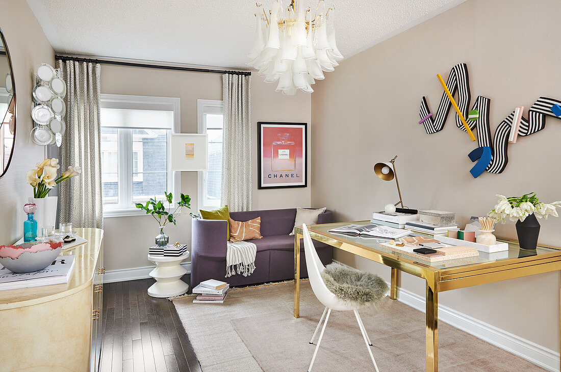 Brass desk with glass top, white chair with fur cushion and purple sofa in study