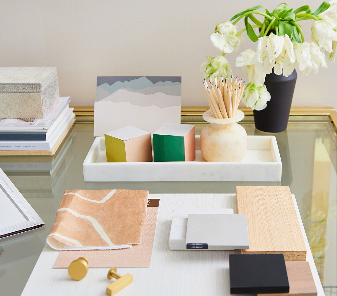 Flowers and stationary on top of brass and glass desk