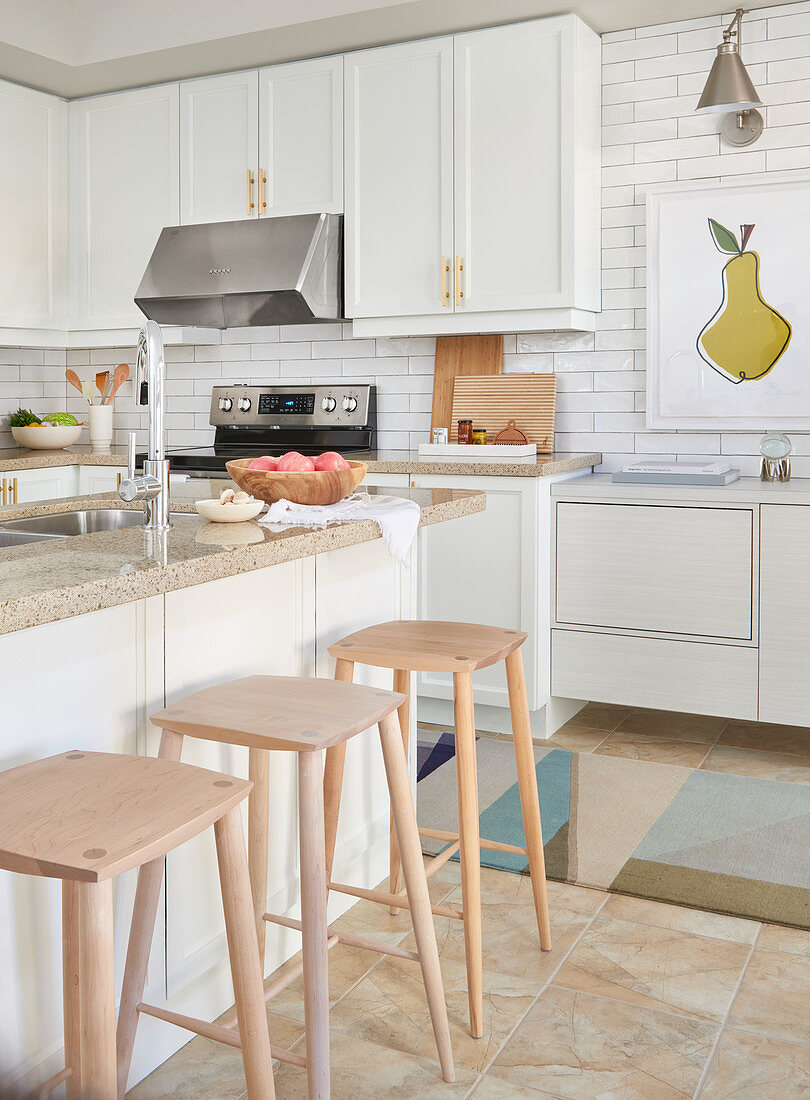 White kitchen with light wood accents, white subway tiles and island counter with light wooden bar stools