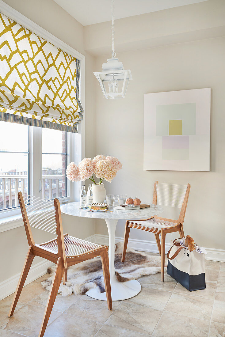 Breakfast nook in kitchen with abstract graphic art work, Roman blind and lantern lamp