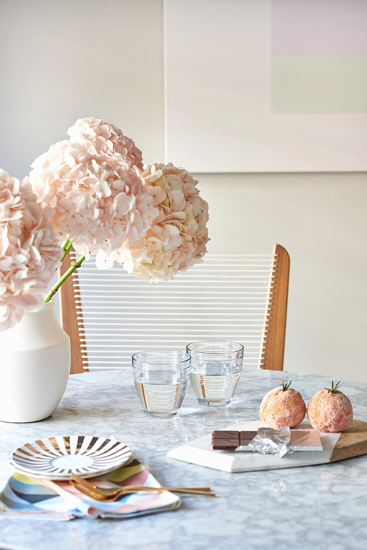 Pink flowers and glasses of water on marble breakfast table and pastries on board