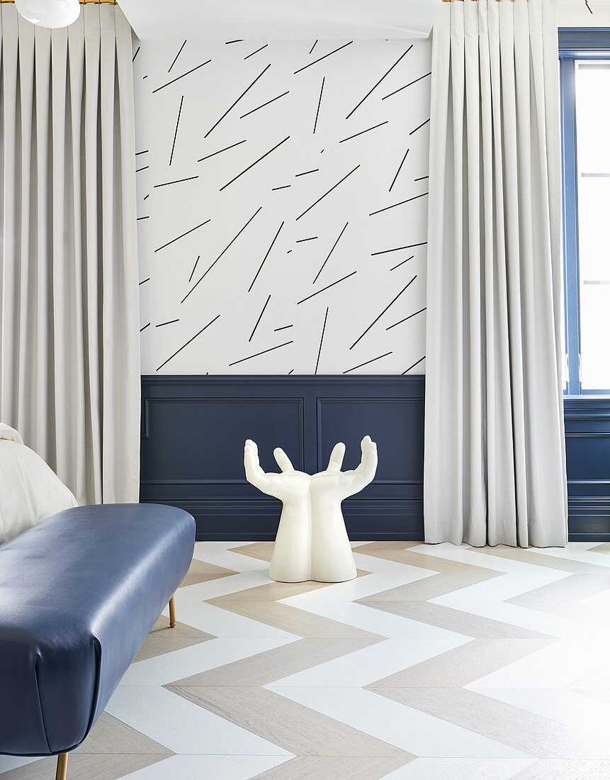 Hand-shaped chair in bedroom with blue wainscoting