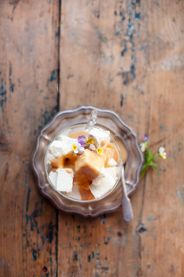 Vanilla ice cream with caramel sauce and viola flowers