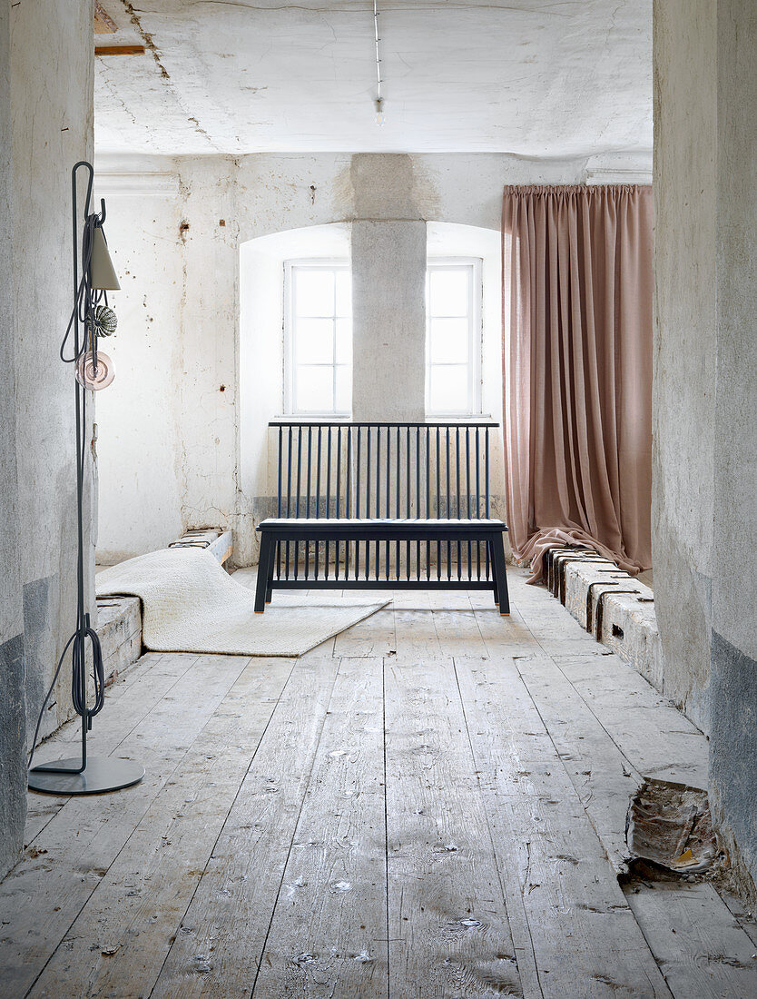 Black wooden bench with upright laths in vintage interior