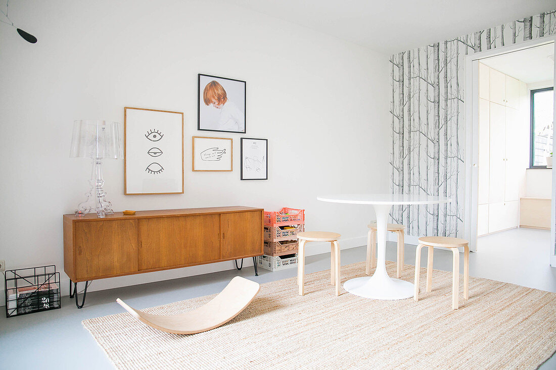 Baby bouncer, round table and retro sideboard in playroom