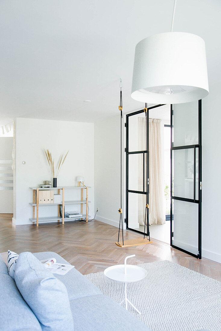Swing and glass-and-steel door in minimalist living room