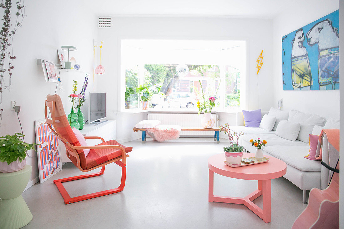 White, light-flooded living room with bright accents of colour