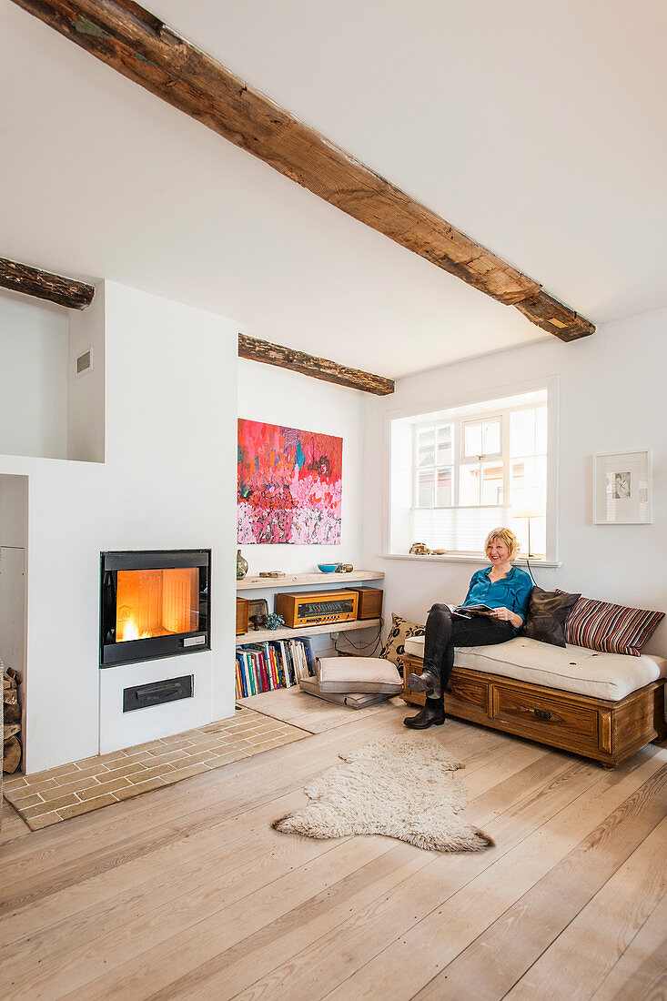 Woman sitting on sofa in bright living room with wooden floor and fireplace